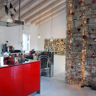 Idee per una cucina parallela industriale con ante lisce, ante rosse, top in acciaio inossidabile, isola, pavimento grigio e top grigio