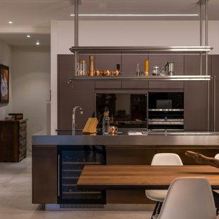 Idee per una grande cucina design con lavello sottopiano, ante lisce, ante grigie, top in acciaio inossidabile, elettrodomestici da incasso, pavimento in gres porcellanato, isola, pavimento grigio e top grigio