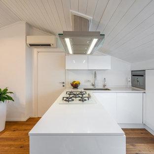 Idee per una cucina nordica con lavello sottopiano, ante lisce, ante bianche, paraspruzzi bianco, pavimento in legno massello medio, penisola e top bianco