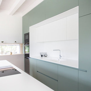 Photo of a scandinavian galley kitchen in Other with an integrated sink, green cabinets, white splashback, black appliances, with island and white benchtop.