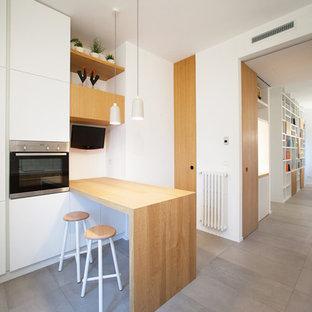 Ispirazione per una cucina minimal con pavimento grigio, ante lisce, ante bianche, top in legno, elettrodomestici in acciaio inossidabile e penisola