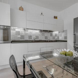 Ispirazione per una cucina minimal di medie dimensioni con lavello sottopiano, ante lisce, ante bianche, paraspruzzi multicolore, paraspruzzi con piastrelle in ceramica, elettrodomestici in acciaio inossidabile e parquet chiaro
