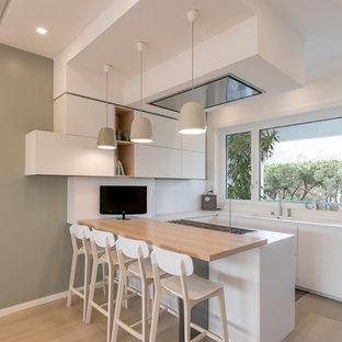 Foto di una cucina ad U contemporanea con ante lisce, ante bianche, paraspruzzi bianco, parquet chiaro, paraspruzzi con lastra di vetro, penisola e top bianco