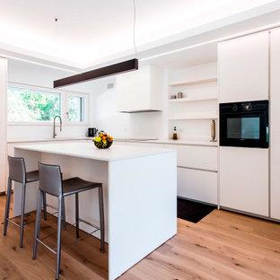 Cette image montre une cuisine design en L avec un évier 1 bac, un placard à porte plane, des portes de placard blanches, un électroménager noir, un sol en bois clair, un îlot central, un plan de travail blanc et un plafond décaissé.