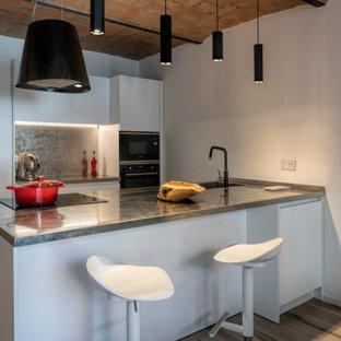 Idee per una cucina parallela minimal con lavello integrato, ante lisce, ante bianche, top in acciaio inossidabile, paraspruzzi a effetto metallico, elettrodomestici neri, pavimento in legno massello medio, penisola, pavimento marrone, top grigio e soffitto a volta