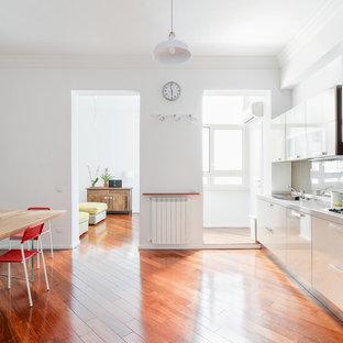 Foto di una grande cucina contemporanea con ante lisce, nessuna isola, pavimento marrone, ante beige, paraspruzzi marrone e pavimento in legno massello medio