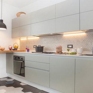 Idee per una cucina lineare minimal con lavello da incasso, ante lisce, ante bianche, top in superficie solida, paraspruzzi multicolore, paraspruzzi con piastrelle in ceramica, elettrodomestici in acciaio inossidabile e pavimento con piastrelle in ceramica
