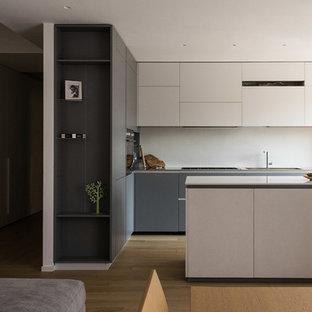 Esempio di una cucina minimalista di medie dimensioni con lavello integrato, ante lisce, ante grigie, top in acciaio inossidabile, paraspruzzi bianco, elettrodomestici in acciaio inossidabile, parquet chiaro e isola