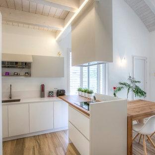 Idee per una cucina nordica di medie dimensioni con ante lisce, ante bianche, top in legno, paraspruzzi bianco, isola, lavello sottopiano, pavimento in legno massello medio e pavimento marrone
