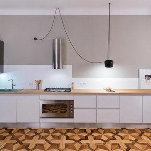 他の地域の巨大なコンテンポラリースタイルのおしゃれなキッチン (シングルシンク、フラットパネル扉のキャビネット、白いキャビネット、木材カウンター、白いキッチンパネル、シルバーの調理設備、無垢フローリング、アイランドなし) の写真