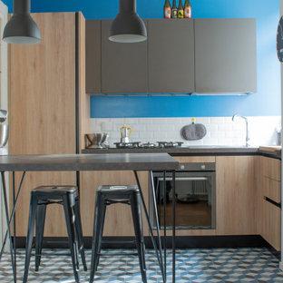 Kleine Moderne Wohnküche in L-Form mit Waschbecken, hellen Holzschränken, Laminat-Arbeitsplatte, Küchenrückwand in Weiß, Rückwand aus Porzellanfliesen, Küchengeräten aus Edelstahl, Porzellan-Bodenfliesen, Halbinsel, blauem Boden, grauer Arbeitsplatte und flächenbündigen Schrankfronten in Rom