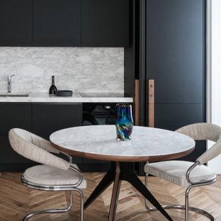 Foto di una cucina lineare contemporanea di medie dimensioni con lavello sottopiano, ante lisce, ante nere, paraspruzzi grigio, elettrodomestici da incasso, parquet chiaro, nessuna isola, pavimento beige e top grigio