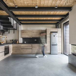 Foto di una cucina a L country con ante lisce, ante in legno chiaro, paraspruzzi nero, elettrodomestici in acciaio inossidabile, pavimento in cemento, nessuna isola, pavimento grigio e top nero