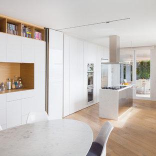 Foto di una cucina abitabile design con ante lisce, ante bianche, top in marmo, elettrodomestici in acciaio inossidabile, isola, lavello sottopiano e parquet chiaro