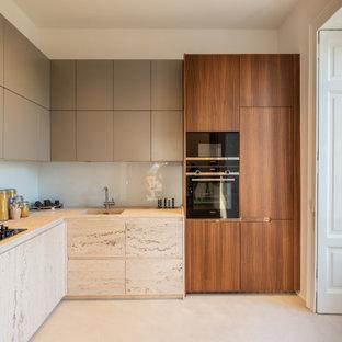 Ispirazione per una cucina a L contemporanea con lavello sottopiano, ante lisce, ante grigie, elettrodomestici neri, nessuna isola, pavimento beige e top bianco