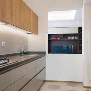 Ispirazione per una cucina parallela contemporanea con ante in legno scuro, nessuna isola, lavello sottopiano, ante lisce, paraspruzzi grigio, elettrodomestici da incasso, pavimento grigio e top nero