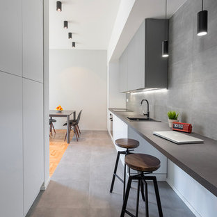 This is an example of a modern galley kitchen in Florence with flat-panel cabinets, grey cabinets, grey splashback, porcelain floors, grey floor, a drop-in sink, black appliances, no island and black benchtop.