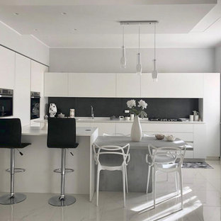 Mid-sized modern u-shaped open plan kitchen in Other with an integrated sink, flat-panel cabinets, white cabinets, solid surface benchtops, black splashback, porcelain splashback, stainless steel appliances, porcelain floors, a peninsula, white floor and white benchtop.