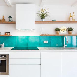 Ispirazione per una cucina costiera con lavello sottopiano, ante lisce, ante bianche, top in marmo e paraspruzzi blu