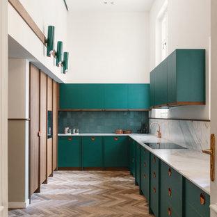 Foto di una grande cucina ad U minimal chiusa con lavello a vasca singola, ante lisce, ante verdi, paraspruzzi verde, elettrodomestici da incasso, nessuna isola, pavimento marrone e top bianco