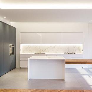 Immagine di una cucina moderna con ante lisce, ante bianche, paraspruzzi bianco e top bianco