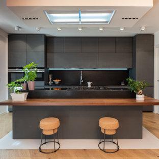 Ispirazione per una cucina parallela design con ante lisce, ante grigie, paraspruzzi nero, elettrodomestici neri, pavimento in legno massello medio, isola e pavimento marrone