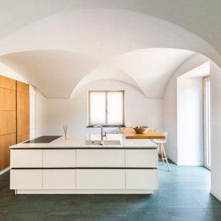 Ispirazione per un cucina con isola centrale mediterraneo con lavello integrato, ante lisce, ante in legno scuro, top bianco e soffitto a volta
