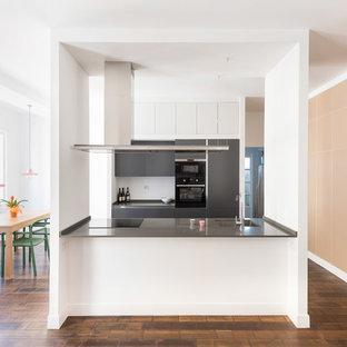 Esempio di una cucina moderna con ante lisce, ante grigie e isola