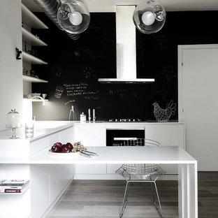Ispirazione per una piccola cucina contemporanea con ante lisce, ante bianche, top in superficie solida, paraspruzzi nero, elettrodomestici neri e pavimento in legno verniciato