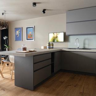 Immagine di una cucina contemporanea di medie dimensioni con lavello a doppia vasca, ante lisce, ante grigie, pavimento in legno massello medio, penisola, top grigio, top in marmo e pavimento marrone