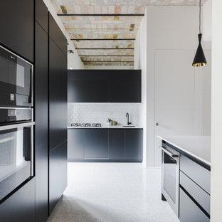 Immagine di una grande cucina ad U design con lavello sottopiano, ante lisce, ante nere, paraspruzzi bianco, paraspruzzi con piastrelle diamantate, elettrodomestici da incasso, isola, pavimento grigio e top bianco
