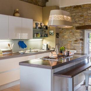 Idee per una piccola cucina minimal con ante bianche, isola, lavello integrato, ante lisce, top in legno, paraspruzzi bianco, elettrodomestici in acciaio inossidabile, pavimento in gres porcellanato e pavimento beige