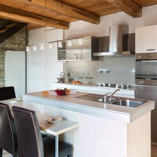 Esempio di una piccola cucina minimal con ante bianche, isola, lavello da incasso, nessun'anta, paraspruzzi grigio, elettrodomestici in acciaio inossidabile, top in laminato e pavimento beige