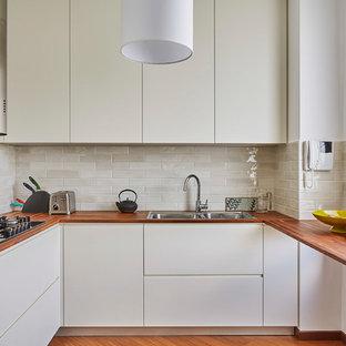 Immagine di una cucina ad U contemporanea chiusa e di medie dimensioni con lavello a doppia vasca, ante lisce, ante bianche, top in legno, paraspruzzi beige, paraspruzzi con piastrelle in ceramica, elettrodomestici in acciaio inossidabile e nessuna isola