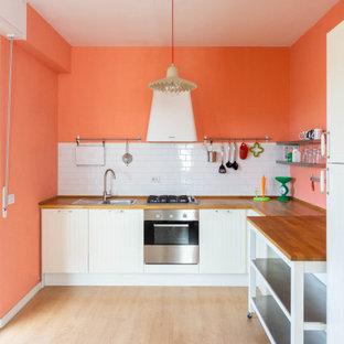 Idee per una grande cucina design con lavello a vasca singola, ante in stile shaker, ante bianche, top in legno, paraspruzzi bianco, paraspruzzi con piastrelle in ceramica, elettrodomestici in acciaio inossidabile, isola e top marrone