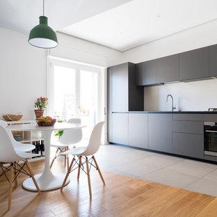 Ispirazione per una cucina minimal con ante lisce, ante grigie, elettrodomestici in acciaio inossidabile, nessuna isola, pavimento grigio e top nero