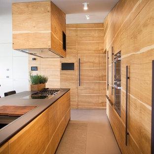 Idee per una cucina a L minimal con ante lisce, ante in legno chiaro, paraspruzzi nero, elettrodomestici da incasso, isola e pavimento beige