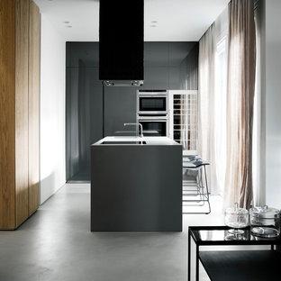 Immagine di una cucina moderna di medie dimensioni con lavello integrato, ante lisce, ante grigie, elettrodomestici in acciaio inossidabile, pavimento in cemento e isola