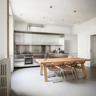 Idéer för ett stort modernt linjärt kök och matrum, med en integrerad diskho, släta luckor, skåp i rostfritt stål, bänkskiva i rostfritt stål, stänkskydd med metallisk yta, stänkskydd i metallkakel, rostfria vitvaror och klinkergolv i porslin
