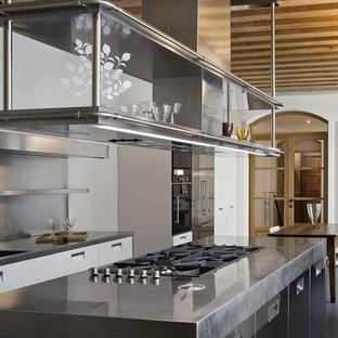 Inredning av ett industriellt linjärt kök och matrum, med en integrerad diskho, luckor med glaspanel, skåp i rostfritt stål, bänkskiva i rostfritt stål, stänkskydd med metallisk yta och en köksö
