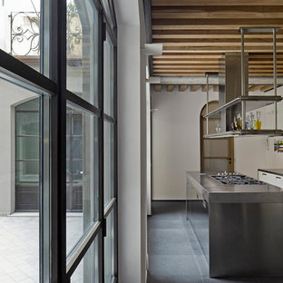 Photo of a mid-sized industrial single-wall kitchen in Milan with an integrated sink, flat-panel cabinets, white cabinets, stainless steel benchtops, grey splashback, metal splashback and with island.
