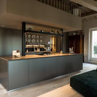 Immagine di una cucina ad ambiente unico design con ante lisce, ante grigie, parquet chiaro, isola, pavimento beige e top grigio