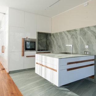 Immagine di una cucina lineare minimal di medie dimensioni con lavello integrato, ante lisce, ante bianche, top in marmo, paraspruzzi verde, paraspruzzi in lastra di pietra, elettrodomestici in acciaio inossidabile, pavimento in marmo e penisola