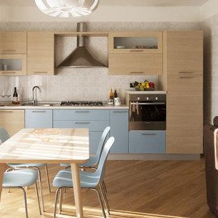 他の地域の中くらいのおしゃれなキッチン (ドロップインシンク、フラットパネル扉のキャビネット、ターコイズのキャビネット、珪岩カウンター、ベージュキッチンパネル、セラミックタイルのキッチンパネル、シルバーの調理設備、淡色無垢フローリング) の写真