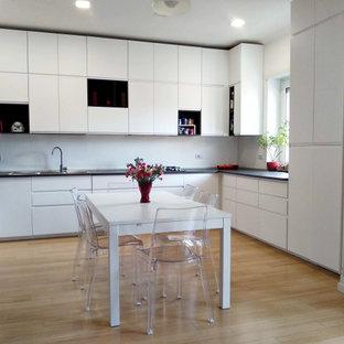 Immagine di una grande cucina minimal con lavello a doppia vasca, ante lisce, ante bianche, top in laminato, elettrodomestici in acciaio inossidabile, parquet chiaro e pavimento beige
