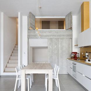 Foto di una cucina design di medie dimensioni con ante lisce, ante bianche, paraspruzzi giallo, nessuna isola, pavimento grigio, lavello da incasso e elettrodomestici bianchi