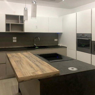 Photo of a small modern l-shaped separate kitchen in Other with a single-bowl sink, flat-panel cabinets, beige cabinets, quartz benchtops, grey splashback, slate splashback, panelled appliances, porcelain floors, with island, multi-coloured floor and black benchtop.