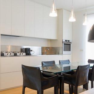 Foto di una cucina lineare design con ante lisce, ante bianche, elettrodomestici in acciaio inossidabile, lavello sottopiano, top in acciaio inossidabile, paraspruzzi grigio, pavimento in legno massello medio, pavimento marrone e top grigio
