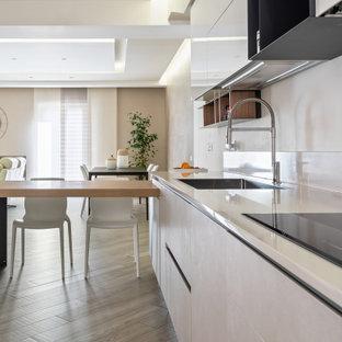Immagine di una cucina contemporanea di medie dimensioni con lavello da incasso, ante lisce, ante bianche, paraspruzzi bianco, elettrodomestici da incasso, pavimento in legno massello medio, penisola, pavimento beige e top bianco