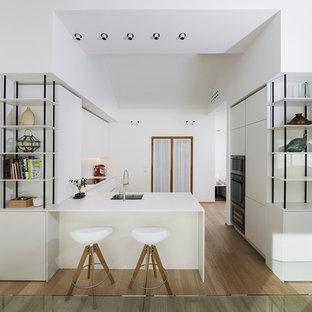 Esempio di una grande cucina a L contemporanea con ante lisce, ante bianche, paraspruzzi bianco, penisola, lavello sottopiano e parquet chiaro